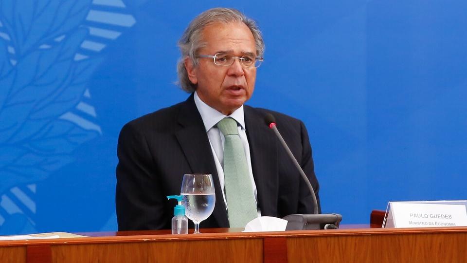 Guedes diz que recuperação da economia está em ritmo interessante: enquadramento médio em Paulo Guedes. Ele está sentado com um microfone em sua frente