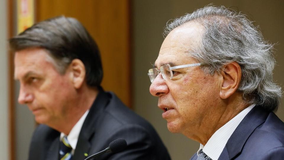 Três a quatro privatizações em até 60 dias: enquadramento em rosto de Paulo Guedes. Ele está com um microfone em sua frente. Ao fundo, é possível ver o presidente Jair Bolsonaro