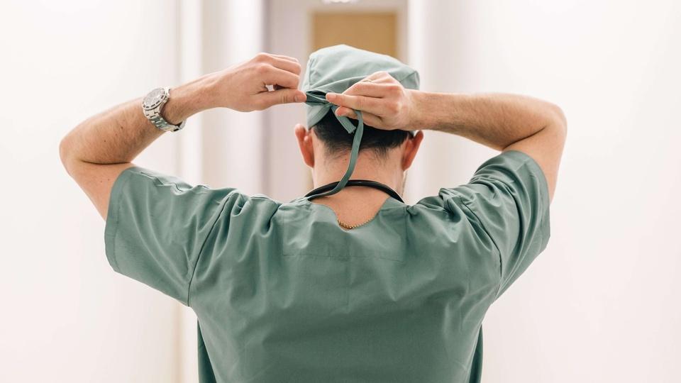 Processo seletivo HCPA: homem de costas vestindo um uniforme hospitalar verde enquanto amarra uma touca verde na cabeça
