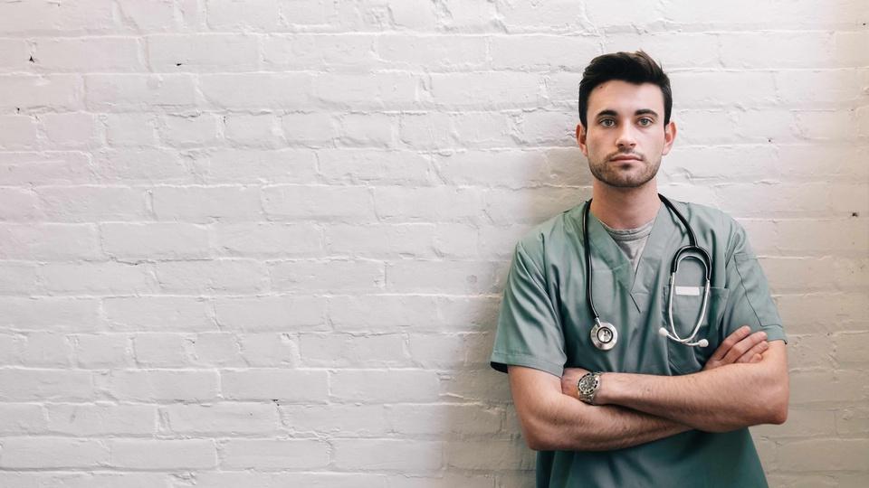 Concurso Hospital Regional de Osasco - foto de um médico uniformizado e encostado em uma parede