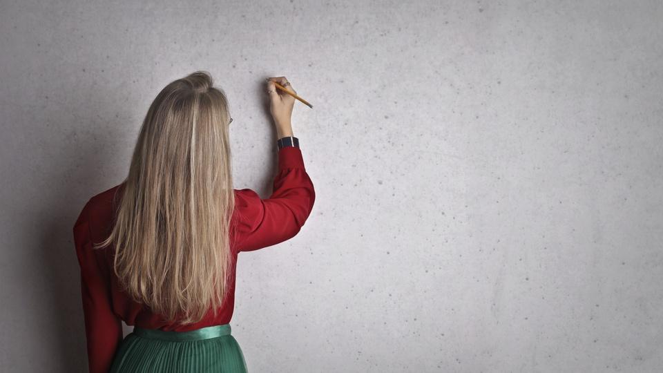 Processo seletivo IBRACEDS - GO: mulher de costas escrevendo em quadro de branco