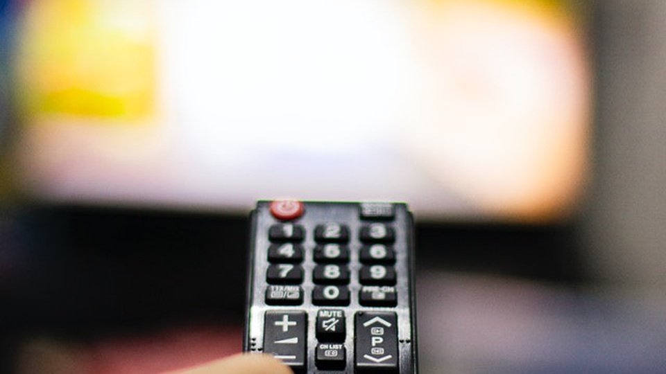 IRDEB BA: imagem de um controle remoto de tv. Ao fundo, uma televisão desfocada