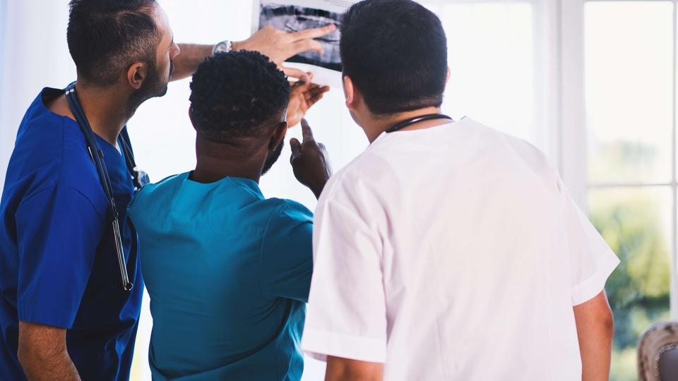 processo seletivo ISGH - CE: a imagem mostra três profissionais da saúde em um consultório olhando uma radiografia
