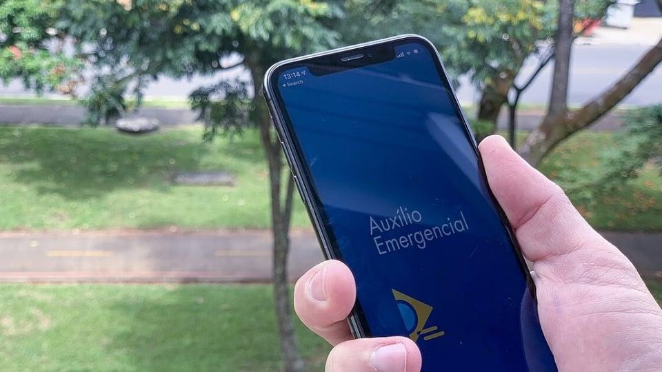 Novo pagamento do auxílio emergencial em 2021: mão segurando celular. No visor, é possível ver a página inicial do programa auxílio emergencial