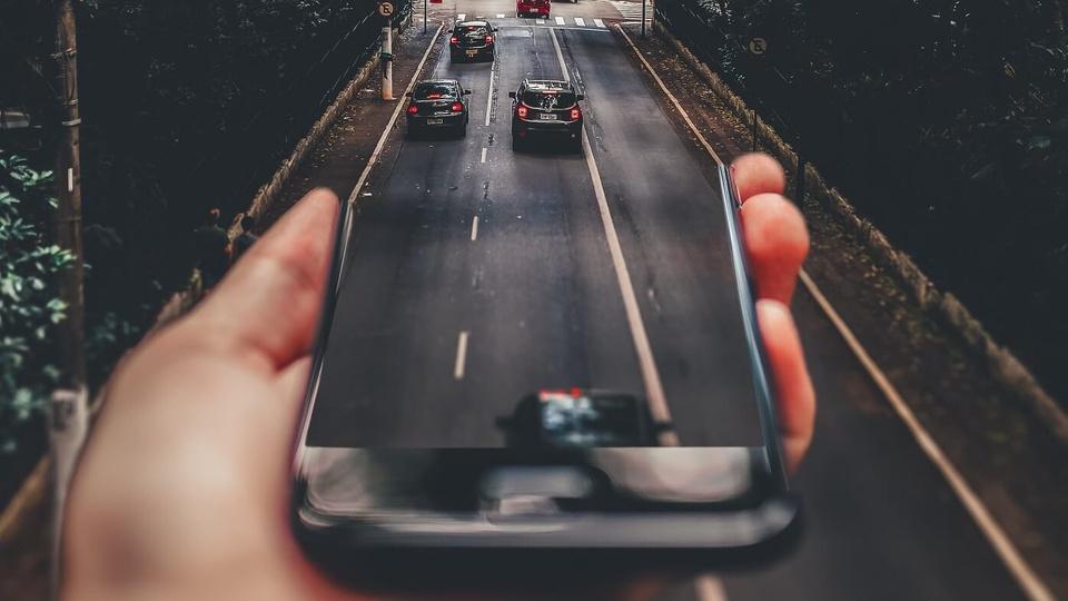 Licenciamento: mão segurando celular que reflete a rua em que vários carros estão passando