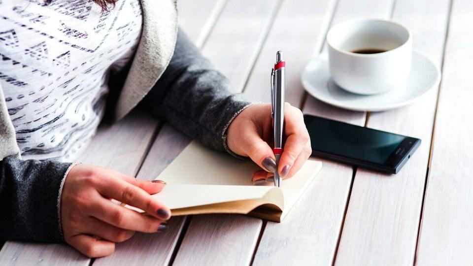 mães de crianças com deficiência cotas: a imagem mostra mulher anotando algo em caderno