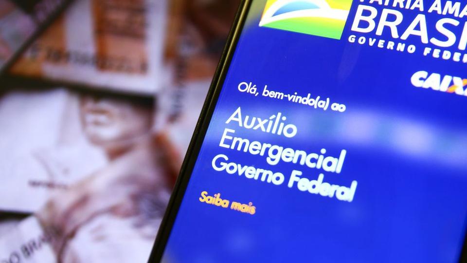 mães solteiras auxílio emergencial: a imagem mostra celular aberto no app do auxílio emergencial e ao fundo notas de dinheiro