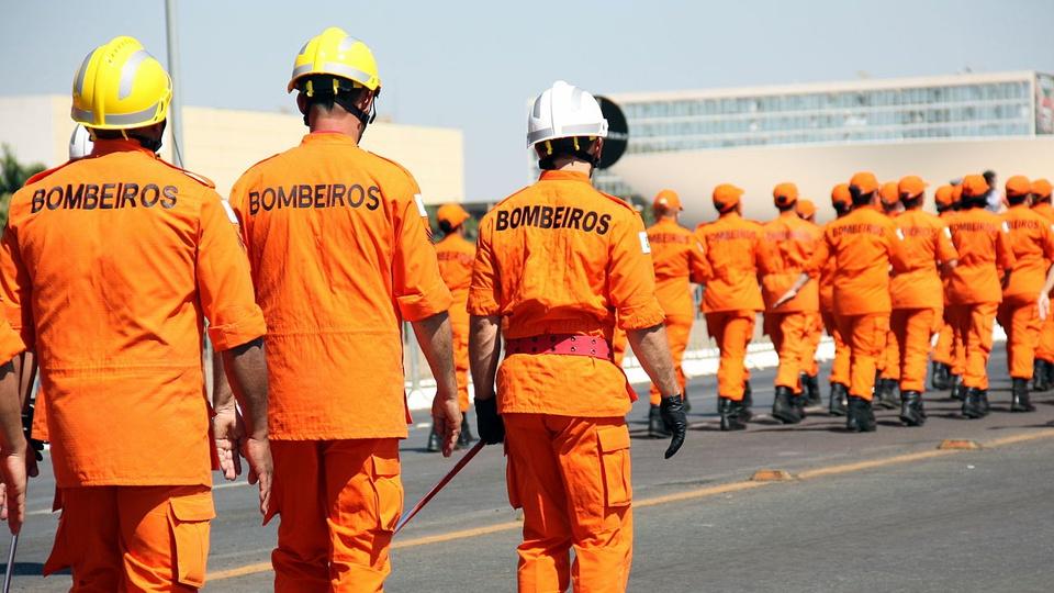 bombeiros e policiais militares serão convocados no DF: vários bombeiros usando uniformes alaranjados e capacetes amarelos andando