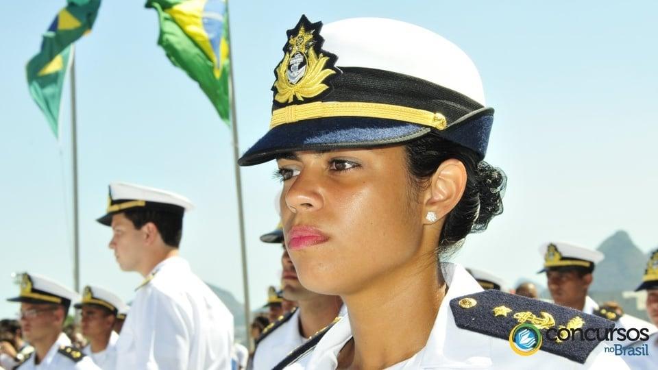 Marinha do Brasil: mulher com uniforme da Marinha. Bandeira do Brasil ao fundo.