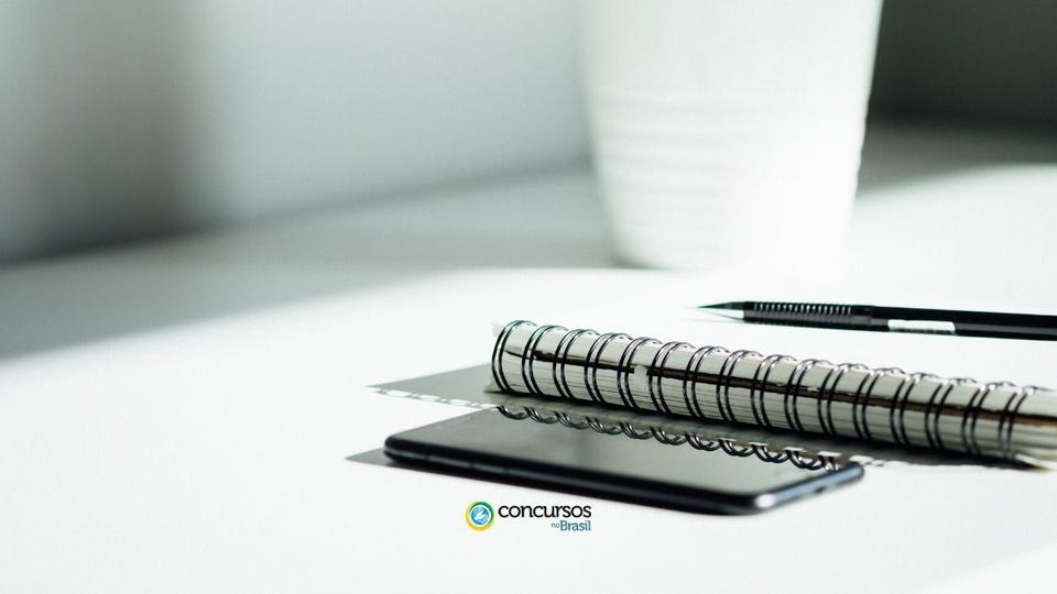 massape do piaui pi: a foto mostra celular, caderno, caneta em uma mesa branca com um vaso branco no plano do fundo