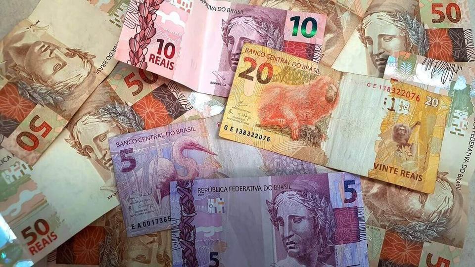 servidores receberam auxílio emergencial indevidamente: várias notas de dinheiro espalhadas