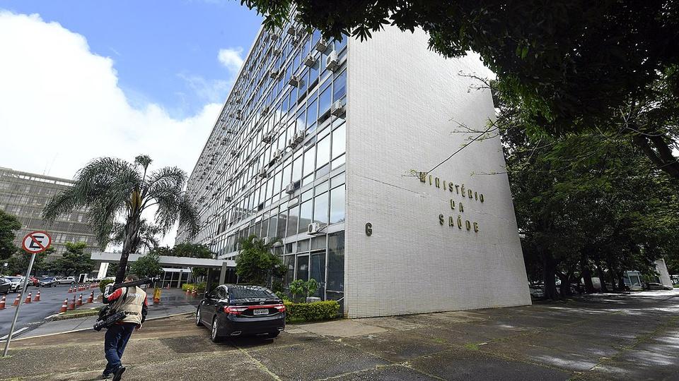 Ministério da Saúde: imagem mostra a fachada do prédio do Ministério da Saúde e estacionamento cheio de carros