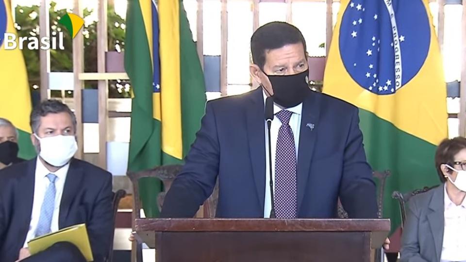 concurso público em órgãos ambientais: Hamilton Mourão usando uma máscara em palanque durante coletiva