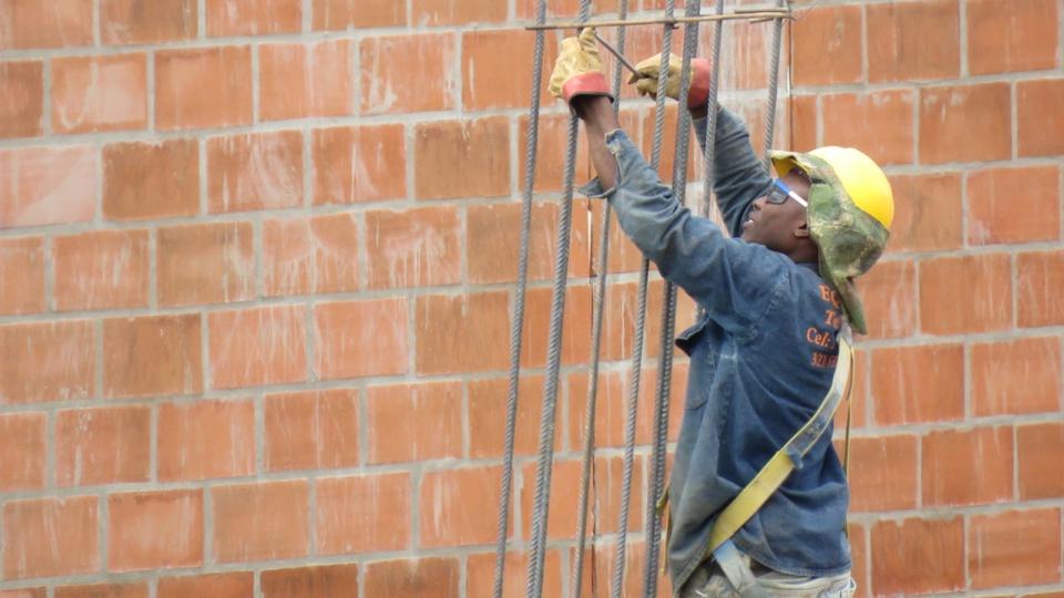 MRV Engenharia abre 100 vagas de emprego em Paulínia: profissional, com capacete de segurança, ajustando estrutura de ferro. No fundo, é possível ver uma parede de tijolos ainda sem acabamento
