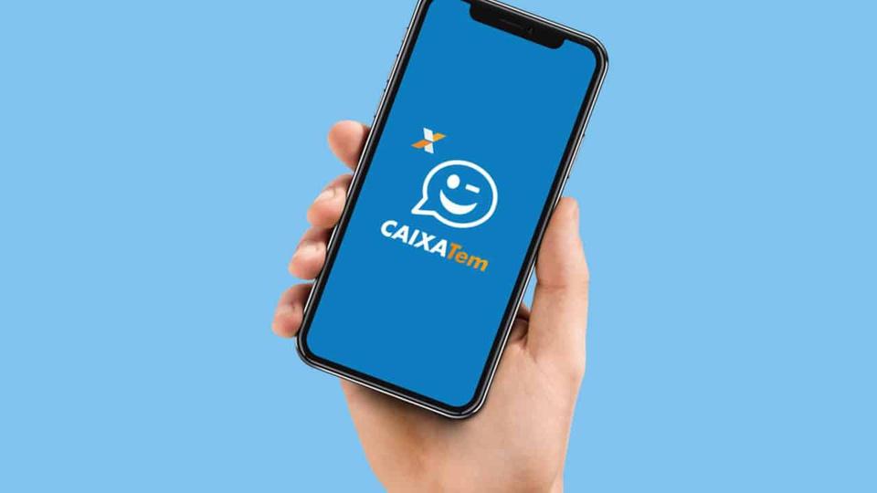 Atualizar Caixa Tem para receber auxílio emergencial: ilustração realista de mão segurando celular. Na tela do aparelho, é possível ver a logo do aplicativo Caixa Tem