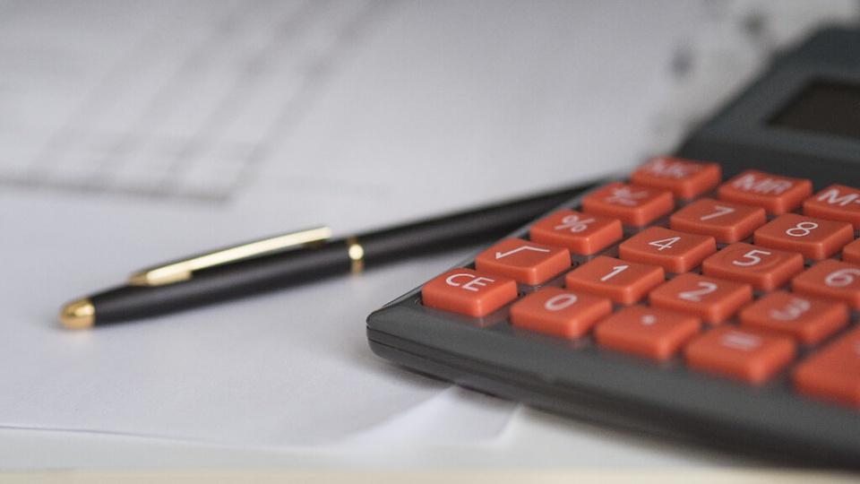 Processo seletivo NavegantesPrev - SC: a foto mostra uma calculadora preta com teclas vermelhas ao lado de uma caneta preta, abaixo da caneta há papéis e tudo está em cima de uma mesa