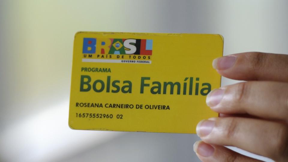 Beneficiários do auxílio emergencial no Bolsa Família de 2021: enquadramento em mão segurando cartão do Bolsa Família