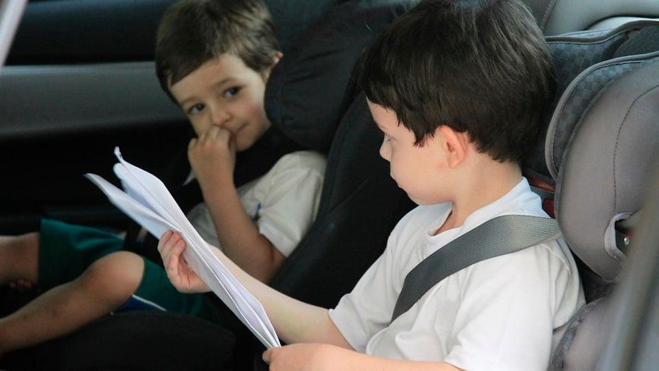 Regras para levar crianças em carros e motos: duas crianças dentro de carro. Elas estão sentadas em cadeirinhas feitas para automóveis