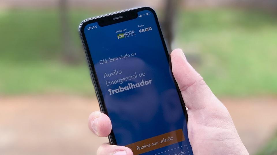 Parcelas do auxílio emergencial 2021: mão segurando celular. Na tela do aparelho, é possível ver a página do programa auxílio emergencial