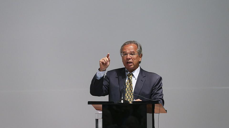 novo auxílio emergencial: a imagem mostra o ministro paulo guedes atrás de palanque falando em microfone e gesticulando com as mãos