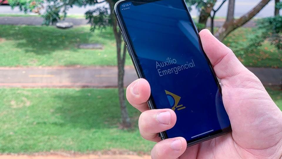 Novo golpe do auxílio emergencial está espalhando nas redes sociais: mão segurando celular aberto no aplicativo do auxílio