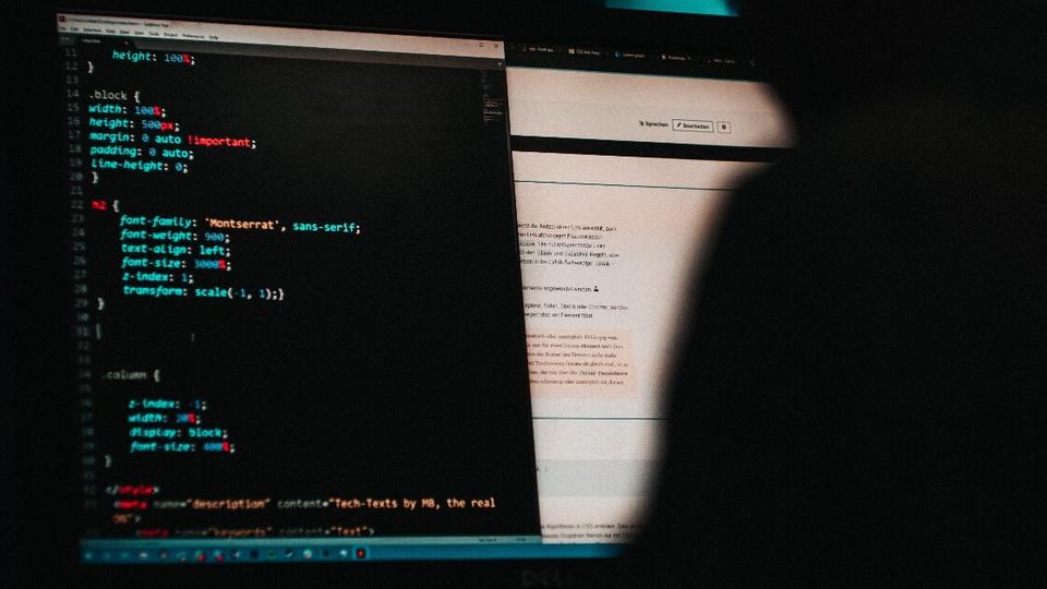 Novo golpe envolvendo auxílio emergencial está sendo feito por e-mail: em ambiente escuro, somente é possível ver a tela de um computador com linhas de código
