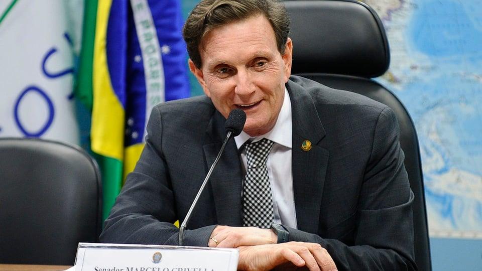 novo órgão do Rio de Janeiro: a imagem mostra marcelo crivella sentado em mesa atrás de microfone com bandeira do brasil ao fundo