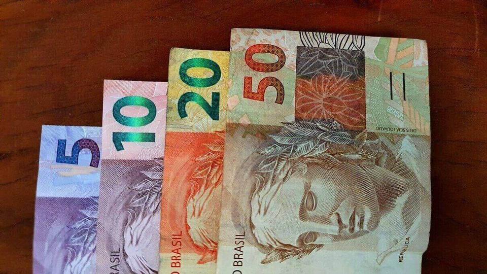saque emergencial do fgts: a imagem mostra notas de 5, 10, 20 e 50 reais enfileiradas