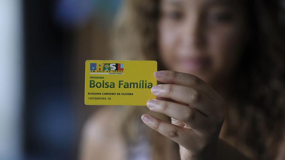 Novo valor do Bolsa Família: enquadramento em mão segurando cartão do Bolsa Família