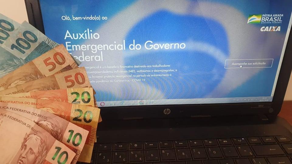 auxílio emergencial 2021: a imagem mostra notas de dinheiro no canto esquerto da tela e computador aberto no site do auxílio emergencial