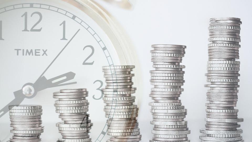 Regime de Previdência Complementar dos Servidores Públicos, pilhas de moedas com relógio no fundo
