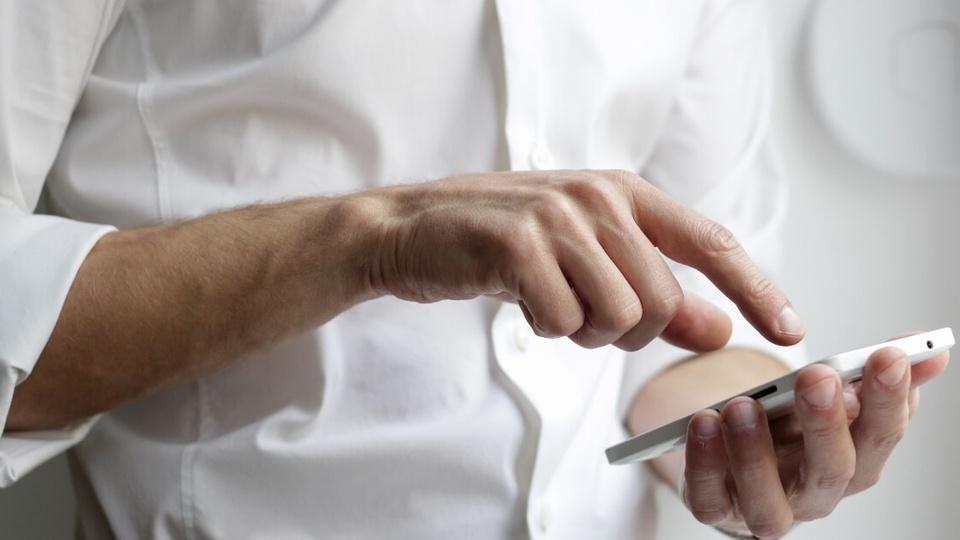 O que fazer para recuperar o saque do FGTS suspenso: enquadramento fechado em homem digitando em celular. Não é possível ver o seu rosto