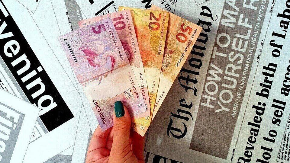 Renda Brasil: mão segurando notas de dinheiro num fundo de jornal