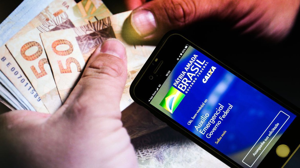 Pagamento do auxílio emergencial 2021: mão segurando dinheiro. Do lado, é possível ver um celular com a tela aberta na página do auxílio emergencial