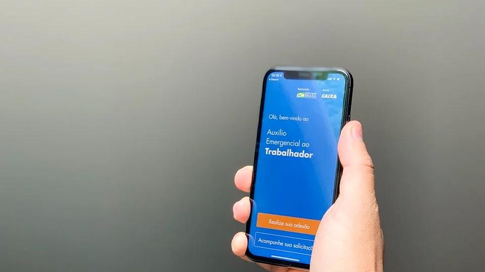 Pagamento do auxílio emergencial 2021: mão segurando celular. Na tela do aparelho, é possível ver a página do auxílio emergencial