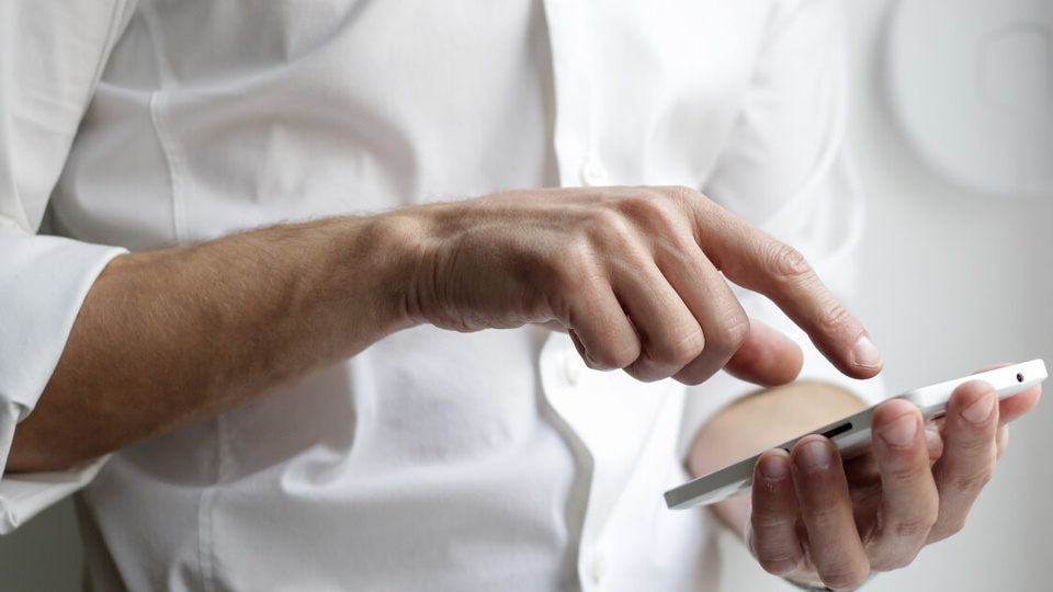 Pagar o IPTU durante pandemia: enquadramento fechado nas mãos de um homem enquanto mexe em celular