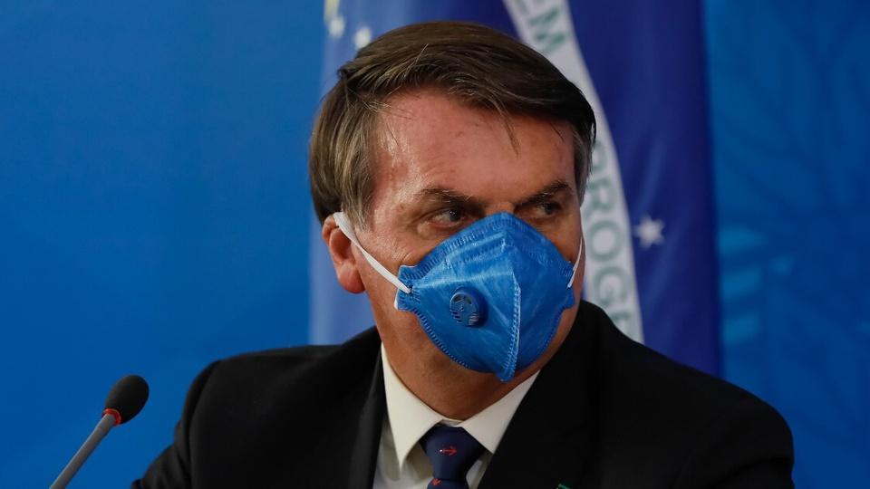 Bolsonaro culpa estados pelos milhões de novos desempregados: enquadramento em rosto de Jair Bolsonaro. Ele está usando uma máscara hospitalar na cor azul