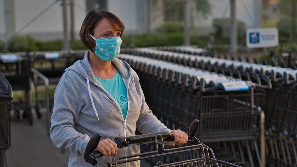 mulheres são as mais afetadas pela crise: mulher usando máscara cirúrgica empurrando carrinho de supermercado