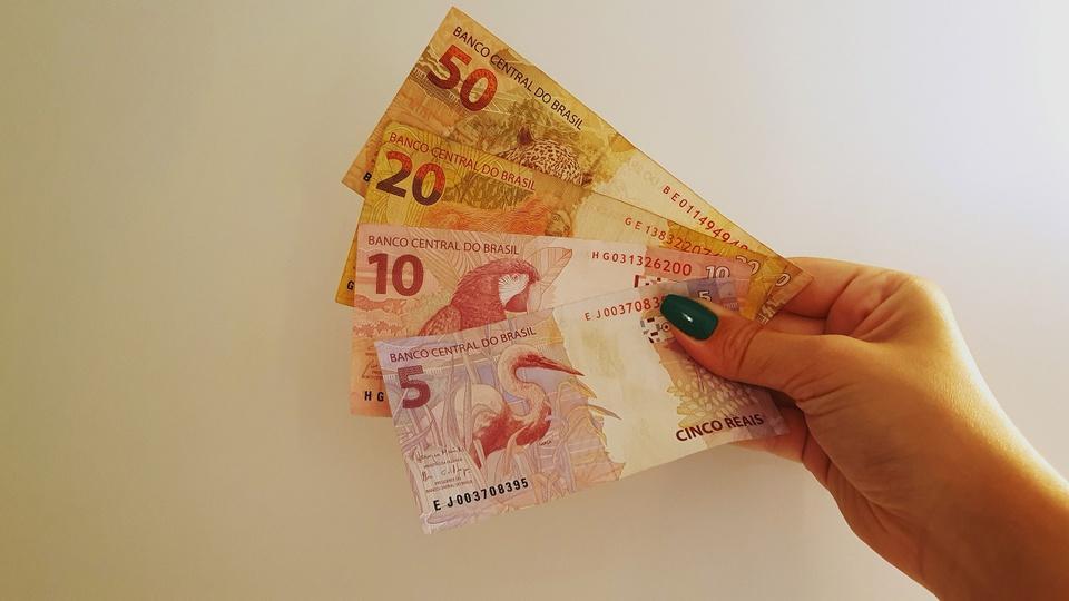 13º salário: a imagem mostra mão segurando leque de notas de 50, 20, 10 e 5 reais