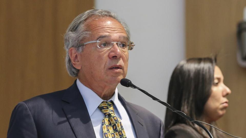 País deve seguir com reformas estruturais: é possível ver Paulo Guedes se pronunciando. Um microfone está em sua frente
