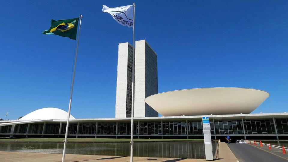 pec emergencial: a imagem mostra o congresso nacional com duas bandeiras hasteadas na frente, sendo uma do brasil e outra do mercosul