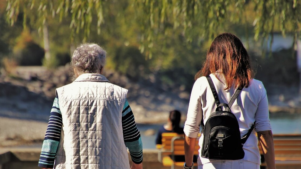 Qual o prazo para o INSS analisar um pedido de aposentadoria: de costas para a câmera, duas mulheres andam em ambiente aberto. Uma delas é jovem e a outra tem idade avançada