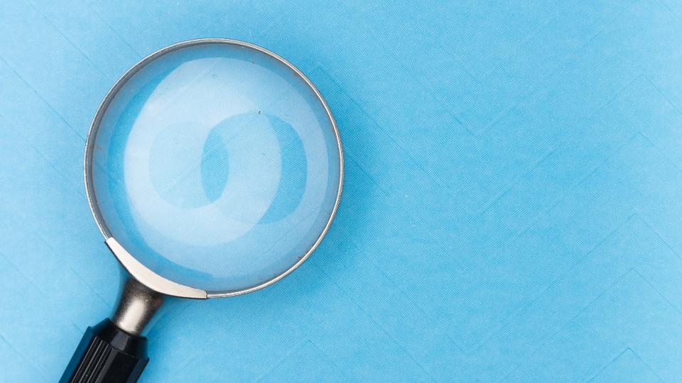 Perfil da banca organizadora do concurso: ilustração realista de uma lupa. num fundo azul claro