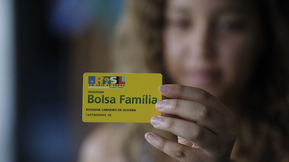 PL cria benefícios emergenciais dentro do Bolsa Família: enquadramento em mão segurando cartão do programa Bolsa Família