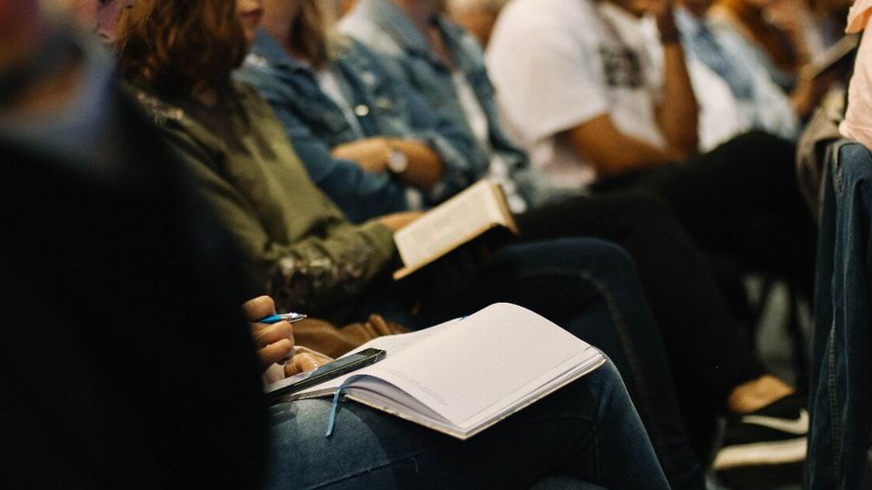Bolsa emergencial para estudantes de instituições privadas: enquadramento fechado em um grupo de estudantes sentados. Um deles está com uma caderneta no colo. É possível ver os alunos do quadril para baixo