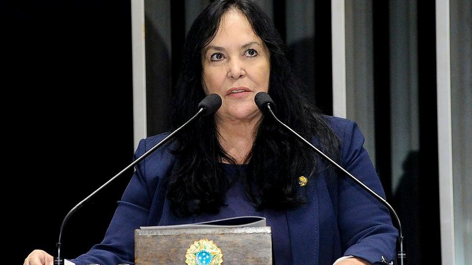 PL suspende dívidas: a imagem mostra a senadora Rose sentada em mesa no plenário do senado atrás de dois microfones.