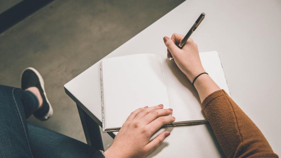 Processo seletivo PC PA: imagem mostra as mãos de uma pessoa segurando uma caneta e escrevendo em um caderno que está em cima de uma mesa