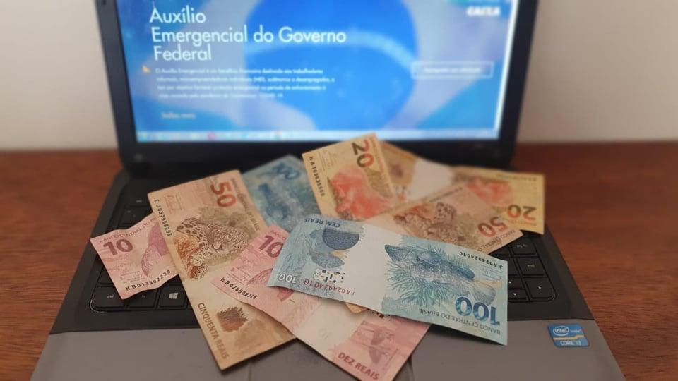 auxílio emergencial 2021: a imagem mostra computador aberto no site do auxílio emergencial e notas de dinheiro espalhadas no teclado