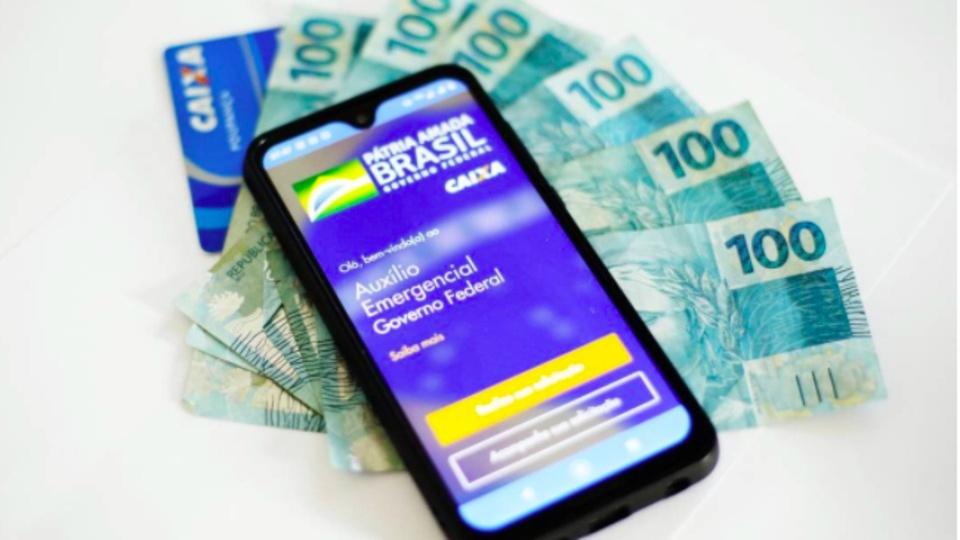 auxílio emergencial: smartphone com cédulas de cem reais
