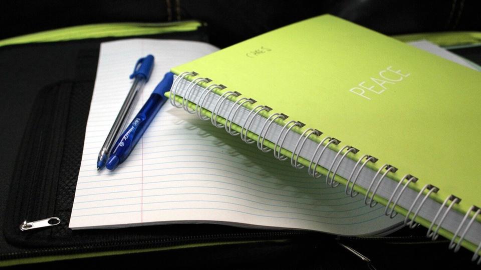 processo seletivo Prefeitura de Cândido Godói: a imagem mostra caderno de capa verde sobre folha de caderno com duas canetas em cima